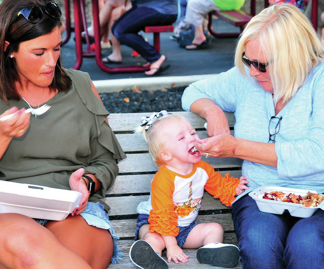 Marissa Wirrig of Bradford watches as Oakleigh Diehl, 15 months, enjoys a Pumpkin Show snack with a little help from her grandmother, Brenda Selanders, at Tuesday's kick-off of the 90th annual Bradford Pumpkin Show.