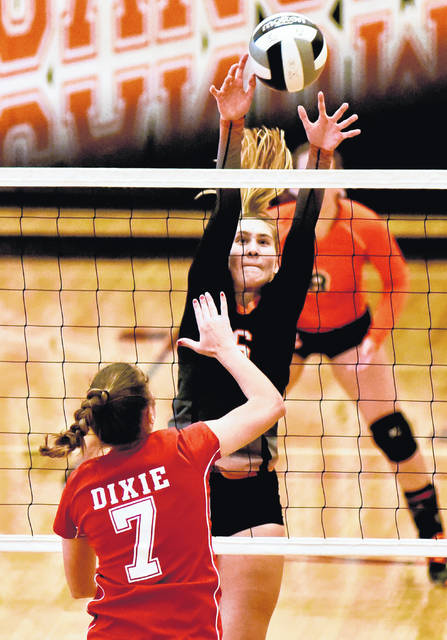Arcanum's Audrey Heiser (6) goes up for a block during a match with New Lebanon Dixie on Monday. The Trojans swept the Greyhounds in three sets.