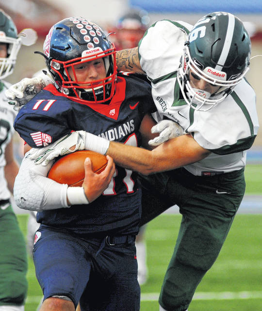 Greenville's Colton Zumbrun (16) tries to tackle Piqua's Micah Karn (11) during their game at Piqua on Friday night. Greenville lost the game, 42-7.