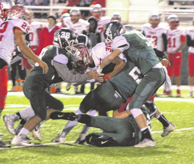 Several Greenville players ganged up to make this tackle during first-half action of the Troy-Greenville football game Friday night at Harmon Field. The Trojans defeated the Green Wave, 48-12.