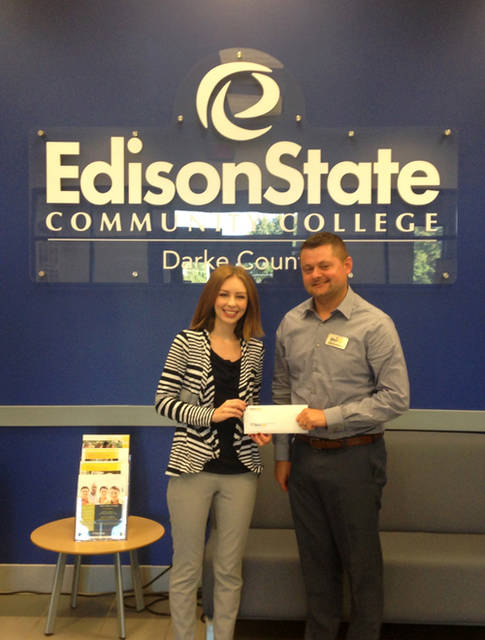Chad Beanblossom, vice president of regional campuses, presents Edison State Community College's donation to Crysta Hutchinson Bloomingdale, executive director of Main Street Greenville.