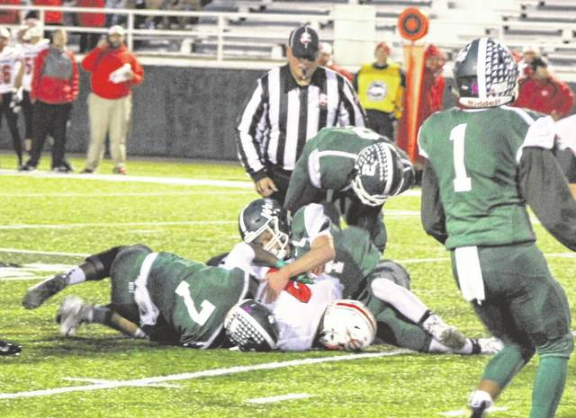 Di'Maurye Ewing (7) and a couple other Greenville defenders are in on a tackle of Tippecanoe's Cade Beam Friday night at Harmon Field. Tippecanoe defeated Greenville, 43-7.