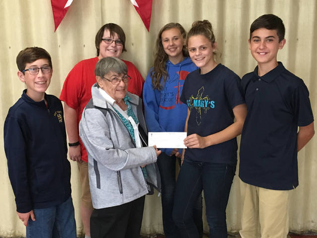 The St. Mary's Student Council Officers present a check to Judy Francis of the Darke County Humane Society. The school had a favorite color day; in order for students to wear their favorite color, they had to bring in a donation for the Humane Society.