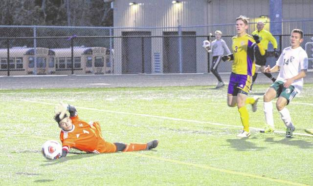 Greenville goalkeeper Jacob Maher dives to knock a Bellbrook shot away from the goal on Monday night in a Division II sectional contest. Bellbrook won the game, 6-0.