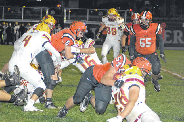 Versailles ball carrier Jake Poling (6) gets wrapped up by several New Bremen defenders during their Midwest Athletic Conference battle on Friday night. New Bremen won the game, 14-7.