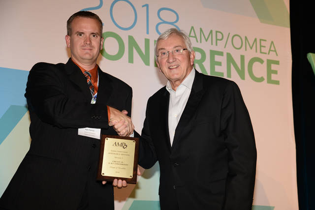 On behalf of the Village of Versailles, Utilities Superintendent Kyle Francis (left) accepts recognition of honorable mention in the System Improvement award category, presented by AMP President/CEO Marc Gerken.