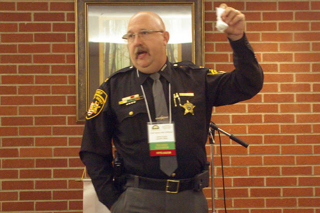 Chief Deputy Mark Whittaker of the Darke County Sheriff's Office holds up a bag representing 19 grams of fentanyl during the Darke County Chamber of Commerce's Good Morning Darke! program on Friday at the Brethren Retirement Community.