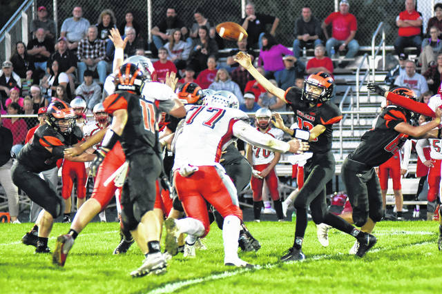 Arcanum quarterback Nick Fry throws a pass during the Trojans home game Friday night against Tri-County North. The Panthers won the game, 30-6.