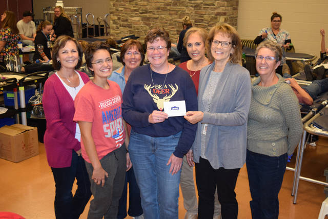 Community Blood Center's Kathy Pleiman and Fort Loramie Community Service Club blood drive volunteers present a $5,000 home improvement gift card to Sharon Holdheide and her daughter, Emily.