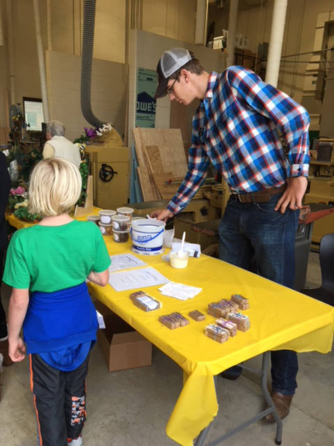 Caden Buschur helped sell Delaney and Noah Barga's goat milk ice cream and soap as a part of their SAE at the Versailles FFA Fall Harvest Sale.