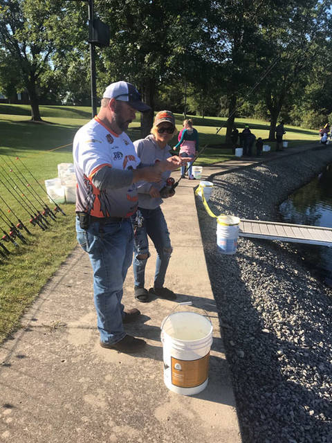 Nakiaya Arrone, daughter of Renee Arrone of Sidney, gets helps getting her fish off the hook from one of the Shelby County BassMasters.