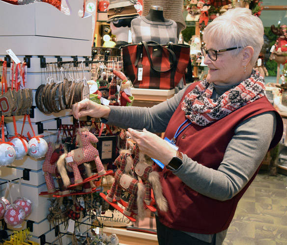 Upper Valley Medical Center volunteer Connie Gillespey arranges holiday items in the hospital gift shop.