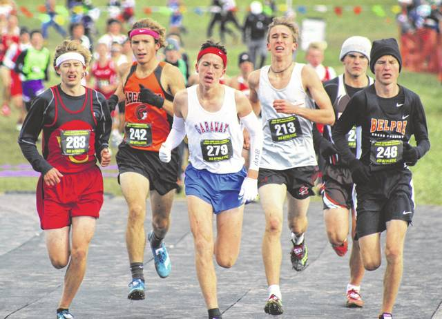 Arcanum senior Tanner Delk (second from left) runs with a group near the top of the leader board on Saturday in the Division III boys state cross country championship race at National Trail Raceway in Hebron. Delk finished fourth overall to earn a spot on the podium.