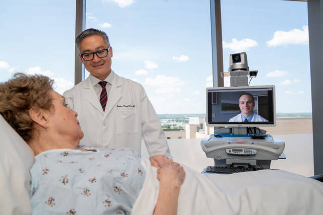 Esteban Cheng-Ching, MD (at left, with patient) and Bryan Ludwig, MD (on the monitor) are both fellowship-trained neurointerventionalist surgeons with the Premier Health Clinical Neuroscience Institute.