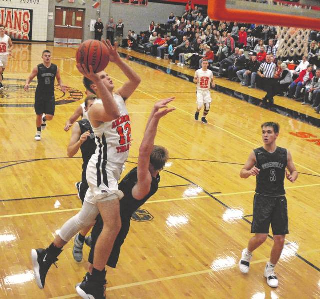 Arcanum's Carter Gray goes in for a shot against Greenville on Saturday night in the Trojans season opener. Gray finished with 11 points and Arcanum won the game, 55-29.