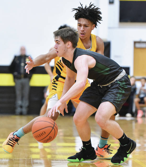 Greenville sophomore guard Reed Hanes dribbles with pressure from Sidney junior guard Darren Taborn during a Greater Western Ohio Conference American North Division game on Friday in Sidney.
