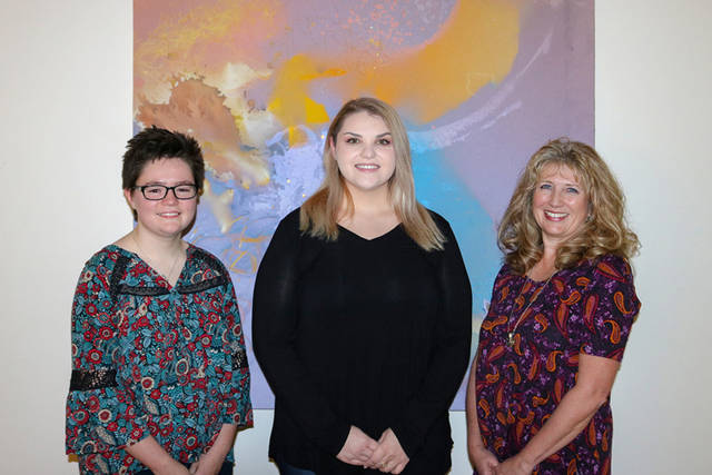 Student editors Gabriella Clingman, Mindy Bach and Kim Kiehl stand in front of artwork created by the late Anne Vacarro.