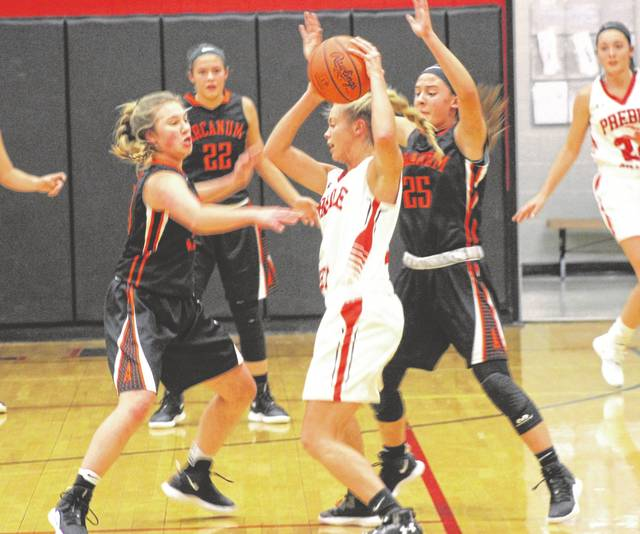 Arcanum's Gracie Garno (left) and Madelyn Fearon double team a Preble Shawnee player in first half action of their non-conference game on Tuesday night at Preble Shawnee. The Lady Trojans won the game, 66-51.