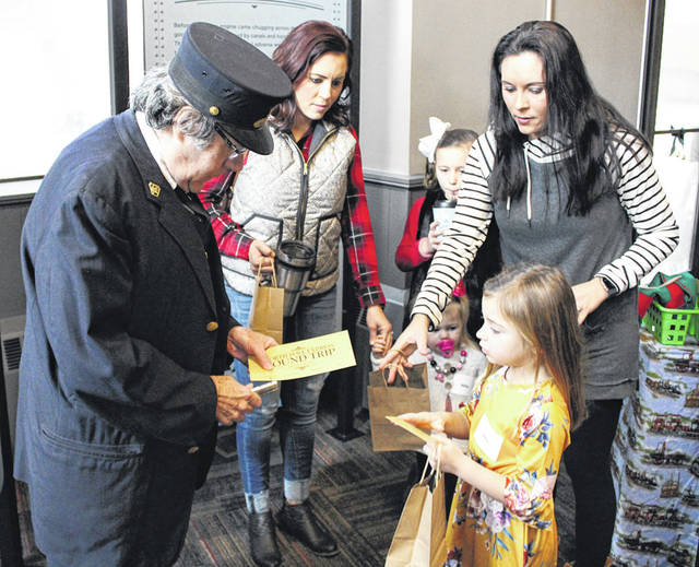 "Volunteer conductor John Edminson punches tickets for children entering the Bradford Railroad Museum's ""North Pole Express."" The museum sold more than 100 tickets for the event, held Saturday."