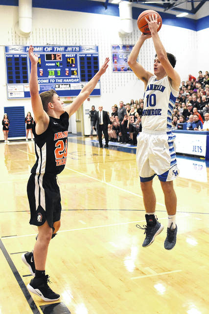 Franklin-Monroe's Jordan Rhoades shoots over an Arcanum defender during the Jets first round battle with the Trojans on Friday night during the Jet Holiday Tournament. FM won the game, 60-54.