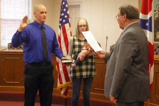 Joseph Wolfe (left) was sworn in as a Greenville police officer by Greenville Mayor Steve Willman (right) on Monday in the Greenville council chambers. Wolfe's girlfriend, Sierra Behnken, held the Bible and their son, Westlyn Wolfe.