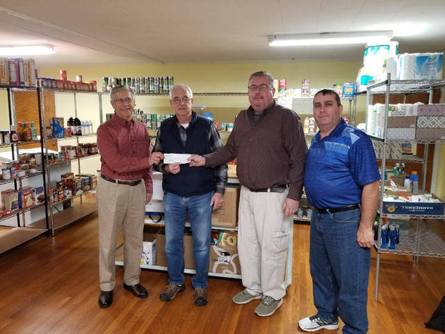 The Versailles Knights of Columbus and Versailles Lions Club presented a check to the Council of Churches food pantry. Pictured are Dave Bey of the Versailles Lions Club, Dan Brown of the Versailles Council of Churches, Brian Heitkamp and Luke Subler of the Versailles Knights of Columbus.