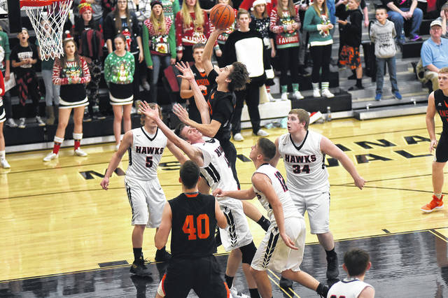 Ansonia's Matthew Farrier puts up a shot with several Mississinawa Valley defenders surrounding him during their Cross County Conference battle on Tuesday night. The Tigers defeated the Blackhawks, 33-25.