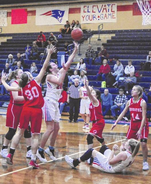 Tri-Village freshman Meghan Downing puts up a shot surrounded by Houston defenders during their non-conference battle on Monday night. The Patriots won the game, 58-32.