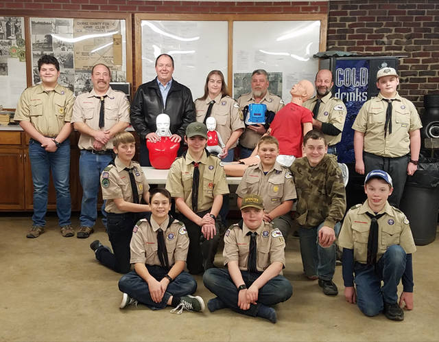 TASKS President Scott Garrison is pictured along with leaders and members of New Madison Troop 96, displaying the CPR mannequins, AED trainer and moulage mannequin.