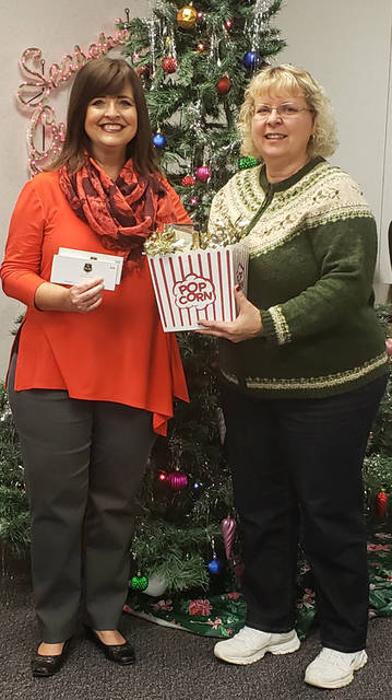 Lisa Martin (left), representing Greenville National Bank, presents a movie night package to Chery Stinson, a winner in The Daily Advocate's 12 Days of Giving.