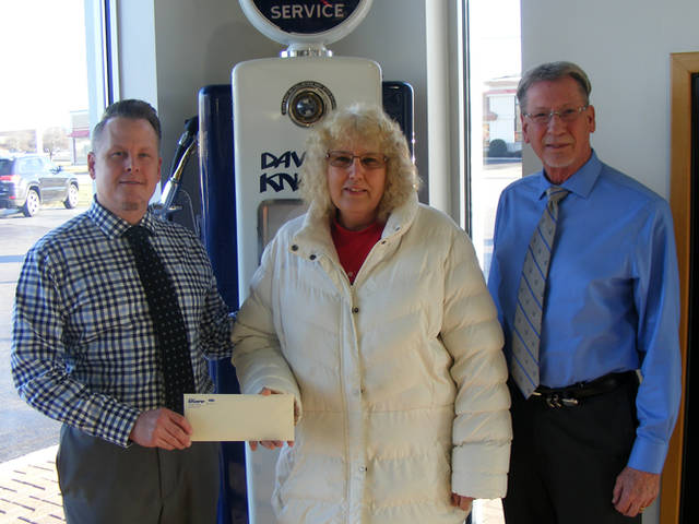 Bryan Knapp (left) and Dave Knapp (right) of Dave Knapp Ford present a $100 gift certificate toward the purchase of a set of tires to Toni Midlam of Ansonia, a winner in The Daily Advocate's 12 Days of Giving.