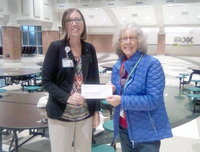 Lauren Henry (left), director of the Wayne HealthCare Foundation, presents a check to Kay Sloat, assistant program coordinator for Empowering Darke County Youth. This is the foundation's second year of support.
