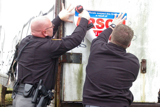Deputy Doug Didier (left) of the Darke County Sheriff's Office and Assistant Fire Chief Shannon Fritz of the Greenville Fire Department place a reward poster on the side of a tractor trailer at 102 Vine St. An arson fire in November damaged the property.