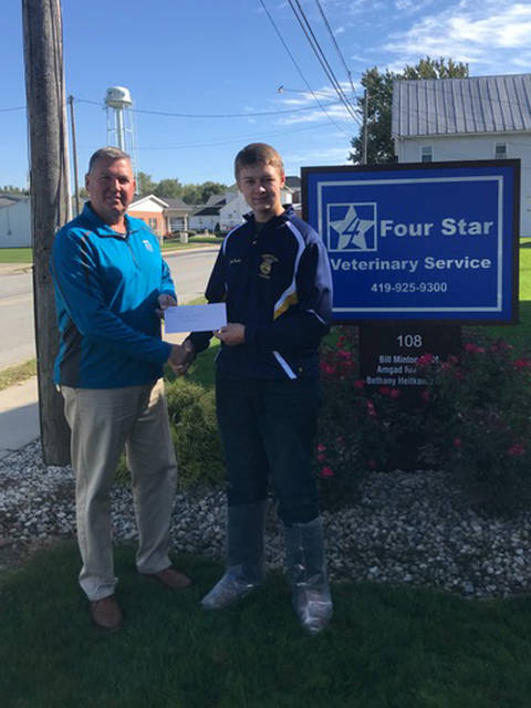 Versailles FFA President Jacob Wuebker is shown receiving a donation from Four Star Veterinary Service LLC, represented by Dr. Bill Minton, as part of the recent Zoetis Program.