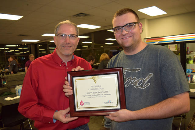 Midmark's Mitch Eiting (left) is pictured with 5,000th donor Mason Kuhn.