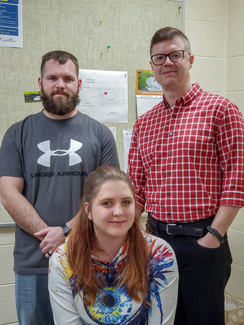 Associate Professor of English William Loudermilk stands with winning essay writers Mitch Bolin and Heidi Bundy.