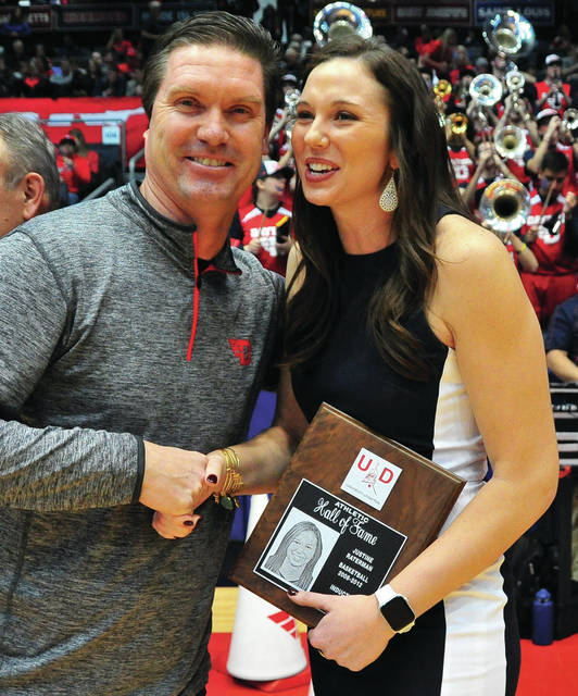 Former Versailles and University of Dayton basketball standout Justine Raterman is congratulated by fellow Hall of Fame member Brian Harlamert after her induction into the University of Dayton Hall of Fame.