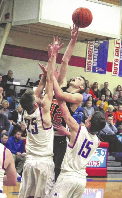 Arcanum's Carter Gray takes a shot over the top of a pair of Tri-Village players in their Cross County Conference battle on Friday night. The Trojans won the game, 60-52.