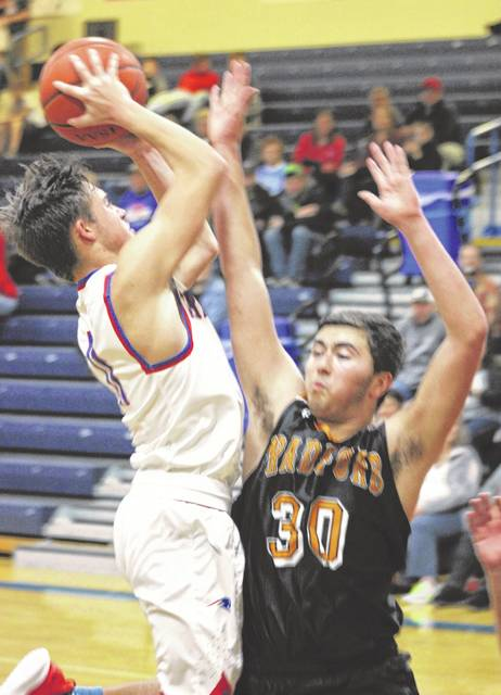 Tri-Village's Derek Eyer goes in for a score against Bradford defender Kegan Fair during their game on Tuesday night. The Patriots won the game, 73-34.