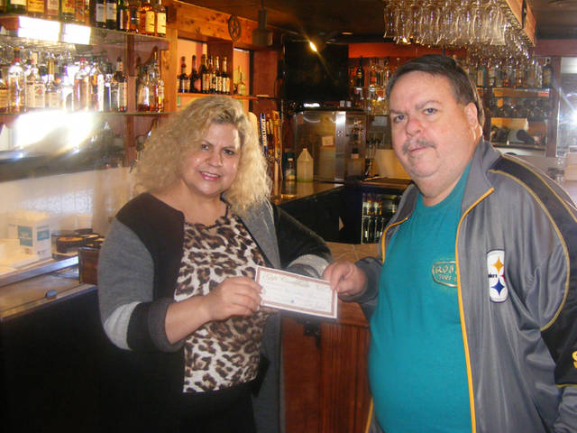 Tina Bandedo (left), owner of El Camino Real, presents a $100 gift certificate to Tom Frazer of Greenville, a winner in The Daily Advocate's 12 Days of Giving.