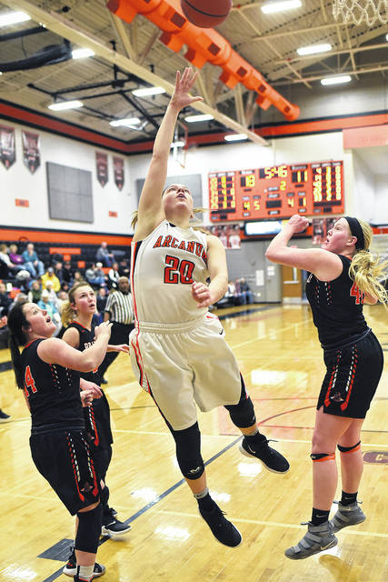 Arcanum's Kayla O'Daniel (20) splits a pair of Bradford defenders as she takes the ball to the basket in a Cross County Conference battle on Tuesday night. O'Daniel had a game-high 17 points and the Trojans won the game, 48-40.