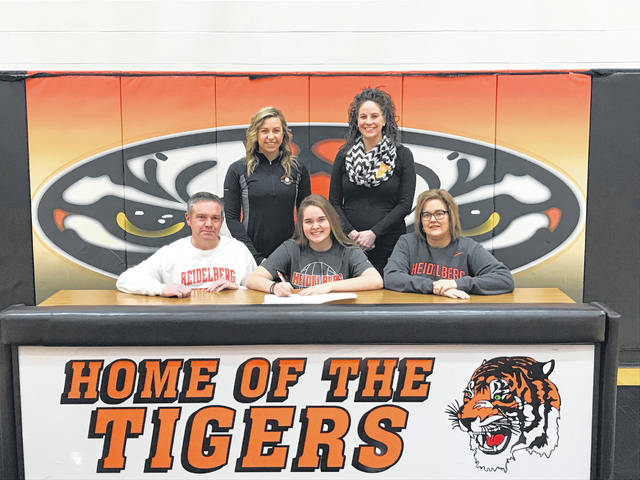 Versailles senior Kelsey Custenborder recently signed her letter of intent to continue playing volleyball at Heidelberg University. Kelsey (seated in center) is pictured with her parents Pat Custenborder (left) and Kim Custenborder (right). Standing (left to right) are Versailles head volleyball coach Kenzie Bruggeman and varsity assistant coach Liz McNeilan.