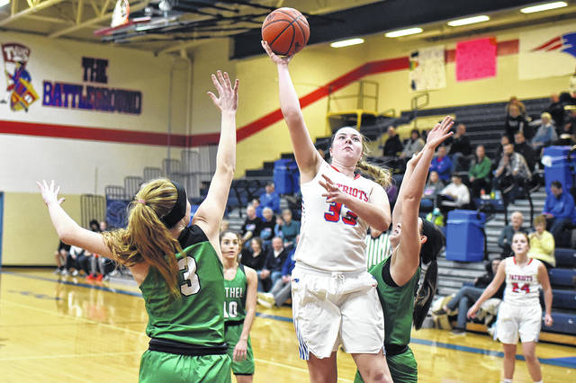 Tri-Village's Maddie Downing scores between a pair of Bethel defenders on Thursday night. The Patriots defeated the Bees, 55-28.