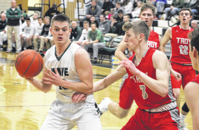 Greenville's Noah Walker (13) was guarded heavily by Troy's Austin Stanaford, but still scored 22 points in the game. However, the Trojans won the Greater Western Ohio Conference contest, 71-43.