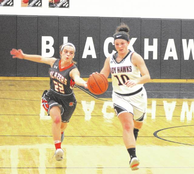 Mississinawa Valley senior Sidnie Hunt brings the ball up the floor being chased by National Trail's Evan Byrd during second half action of their game on Thursday night. The Blazers won the game, 61-41.