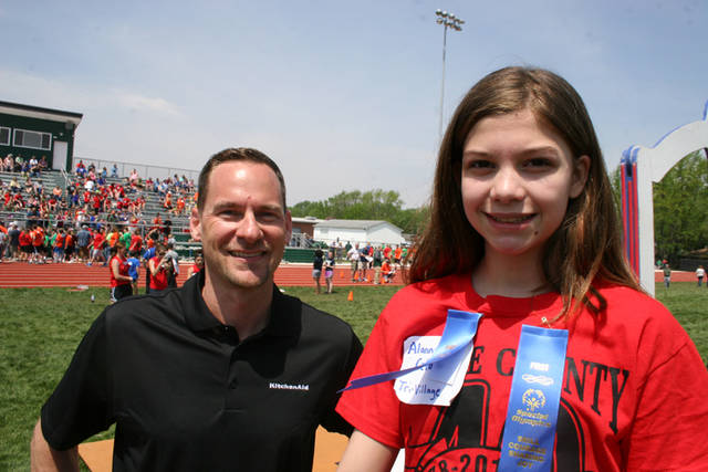 Jason Hollinger from Whirlpool is pictured with Alanna Cela from Tri-Village Elementary after one of her events at last spring's Darke County Special Olympics track and field event. Hollinger presented ribbons to the Special Olympians.