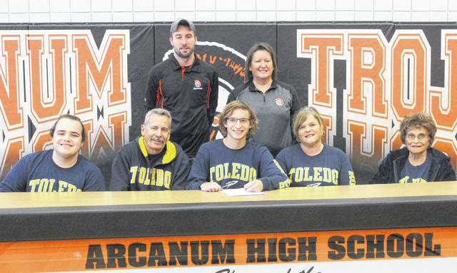 Arcanum senior Tanner Delk (seated center) signed his National Letter of Intent to continue running cross country for the University of Toledo on Thursday. Delk was surrounded by family members (left to right) Tristan Delk, Tim Delk, Teresea Delk and Jean Singleton. Arcanum coaches John Junkins and Chris Kessler are standing in the back.