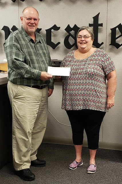 Bill Bixler (left) of The Daily Advocate presents a $100 gift certificate from St. Clair Manor to Angela Sanders of Greenville, a winner in The Daily Advocate's 12 Days of Giving.