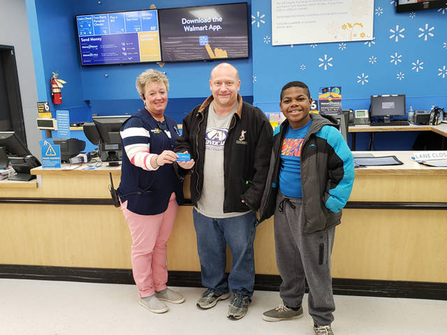 Angie Byers (left), assistant manager of Walmart in Greenville, presents a $100 Walmart gift card to Chuck Runner of Versailles, a winner in The Daily Advocate's 12 Days of Giving. Also present is Chuck's son, Davion Runner (far right).