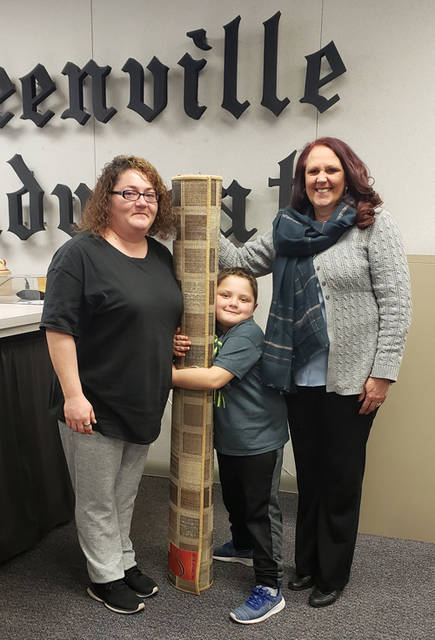 Candy Helm (right), sales rep of The Daily Advocate, presents an area rug donated by Wholesale Carpet Outlet to Stephanie Wagner (left), a winner in The Daily Advocate's 12 Days of Giving. Also present is Wagner's son Kenton (center).
